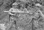Sergeant F. J. Petrie and sapper L. Roberts examining a captured German Panzerschreck weapon, south of Caumont, France, 31 Jul 1944