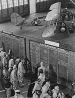 US Navy aviation cadets check flight boards for last minute instructions, Naval Air Training Center, Naval Air Station Corpus Christi, Texas, United States, Nov 1942; note N3N-3 Canary aircraft