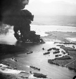 Fully laden United States Navy LSTs burning furiously while other ships flee in Pearl Harbor's West Loch after massive chain-reaction explosions in what became known as the West Loch Disaster, 21 May 1944.
