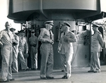 United States Navy Admiral Chester Nimitz, left center, speaking to Rear Admiral Aubrey Fitch on the flight deck of USS Saratoga at Pearl Harbor while an Army Major General, far left, looks on, circa 1942.