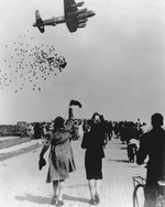 A British Lancaster bomber dropping food parcels for the starving residents of Ypenburg, Netherlands as part of Operation Manna, May 1945.