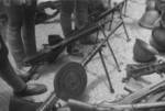 Captured Japanese Type 11 (background), Type 96 (center rear), Type 11 (center front), and DP (foreground with pan) machine guns, Hubei Province, China, 1942; note stocks of Arisaka Type 38 rifles and helmets