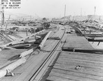 View from the demolished pier looking toward shore and more flattened buildings following a munitions explosion at Port Chicago, California, United States, 17 Jul 1944. 18 Jul 1944 photo.