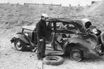 Sailor with bloody face standing next to the car the he was driving when they were both blown off the road by a massive munitions explosion at Port Chicago, California, United States, on 17 Jul 1944. 18 Jul 1944 photo.