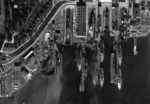 Straight down aerial view of the piers and drydocks at the Puget Sound Naval Shipyard, Bremerton, Washington, United States full of battleships and one carrier, USS Enterprise, 1940.