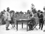 Australian General Sir Thomas Blamey witnessing Japanese Second Army Lt General Fusataro Teshima signing the instrument of surrender for Japanese forces throughout the Dutch East Indies, Morotai, 9 Sep 1945. Photo 1 of 2