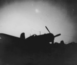 Silhouette of a USMC Corsair fighter seen against a burning supply dump, Yontan Airfield, Okinawa, Japan, Apr 1945
