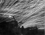 Anti-aircraft tracers in the night sky above Yontan Airfield, Okinawa, Japan, 28 Apr 1945; note US Marine Corps Corsair fighters in foreground