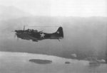 SBD Dauntless dive bomber of US Marine Corps VMSB-144 squadron flying over Cape Torokina by Empress Augusta Bay, Bougainville, Solomon Islands, 1 Nov 1943