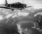 A TBD-1 Devastator bomber flew over Wake Island during the American attack of 24 Feb 1942; note thick smoke in lower center