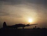 B-17 Flying Fortress bomber at rest, silhouetted by the setting sun, Langley Field, Virginia, United States, Jul 1942; note B-18 Bolo and two A-20 Havoc aircraft in background