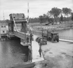 Truck moving across the Caen Canal at Pegasus Bridge, Bénouville, France, 9 Jun 1944; note grounded Horsa glider in background