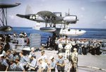 Crew of battleship Missouri performing abandon ship drills, summer 1944; note OS2N-1 Kingfisher aircraft in background on port side catapult