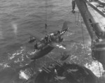 OS2U Kingfisher aircraft being recovered by battleship USS Texas, off Iwo Jima, at 1700 on 16 Feb 1945; note netting of recovery sled hooked on pontoon's recovery hook