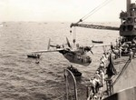 PBM-3D Mariner aircraft of US Navy patrol squadron VP-216 being hoisted onto seaplane tender USS Chandeleur, anapag harbor, Saipan, Mariana Islands, 24 Jun 1944