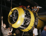 North American Aviation factory workers mounting an engine on a B-25 bomber, Inglewood, California, United States, 1942