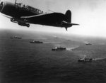 SB2U Vindicator scout bomber flying anti-submarine patrol over an American convoy en route for Capetown, South Africa, 27 Nov 1941; note cruisers Vincennes and Quincy