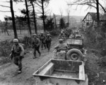 Men of Company C, 1st Battalion, 18th Infantry Regiment, US 1st Infantry Division marching toward Frauwüllesheim, Germany, after crossing the Roer River, 28 Feb 1945