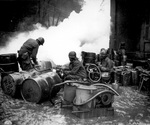 African-American soldiers of the 161st Chemical Smoke Generating Company of the US 3rd Army refilling a M-2 smoke generator, at the Saar River near Wallerfangen, Germany, 11 Dec 1944
