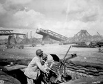 US Army African-American Privates George Cofield and Howard Davis manning an anti-aircraft weapon near a bridge under construction over the Rhine River, 30 Mar 1945