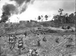 A Company of the Australian 2/23 Infantry Battalion advancing through wrecked oil storage tanks at tank hill, Tarakan, 1 May 1945