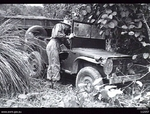 Australian Army Lieutenant MG Searles, 2/25 infantry battalion, inspecting a Japanese Jeep found abandoned on the Milford highway near Popes Track, Balikpapan area, Borneo, 22 Jul 1945