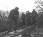 Troops of Company H, 3rd Battalion, 504th Infantry Regiment, US 82nd Airborne Division escorting a captured German SS soldier, Bra, Belgium, 25 Dec 1944