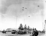 Troops of US 101st Airborne Division watching C-47 Skytrain aircraft delivering supplies to their unit, Bastogne, Belgium, 26 Dec 1944