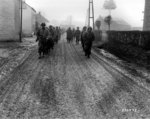 Men of US 28th Infantry Division marching down a street in Bastogne, Belgium, 20 Dec 1944