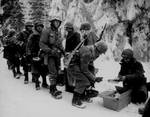 Men of the US 347th Infantry Regiment taking a meal break while en route to La Roche, Belgium, 13 Jan 1945