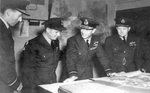 Air Vice Marshal Ralph Cochrane, Wing Commander Guy Gibson, King George VI, and Group Captain John Whitworth discussing Dambusters Raid at St Vincents Hall, headquarters of No. 5 Group RAF Bomber Command, Grantham, England, United Kingdom, 27 May 1943