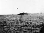 Lexington afire and down at the bow but still steaming and operating aircraft, shortly after she was hit by Japanese torpedoes and bombs during the Battle of Coral Sea, about noon on 8 May 1942