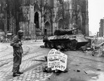 Corporal Luther E. Boger of US 82nd Airborne Division reading a warning sign in front of Cologne Cathedral, Köln (Cologne), Germany, 4 Apr 1945; note Thompson submachine gun and Panther tank wreck
