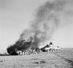 British Crusader tank passing a burning German Panzer IV tank in North Africa during Operation Crusader, 27 Nov 1941