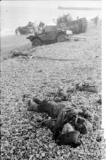 Dead Canadian soldier on the beach after the failed raid on Dieppe, France, Aug 1942; note Daimler Scout Car and Churchill tank in background