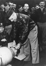 Doolittle wiring a Japanese medal to a bomb, Apr 1942, 1 of 2