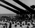 US Navy Chaplain N. D. Lindner leading a memorial service aboard USS South Dakota for men lost to air attacks, off Guam, 1 Jul 1944