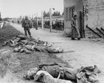 An American soldier standing beside the bodies of SS personnel shot by US troops during the liberation of Dachau Concentration Camp, Germany, 29-30 Apr 1945
