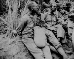 Americans prisoners, with hands tied behind their backs, caught a rare moment of rest on the Bataan Death March, Luzon, Philippine Islands, May 1942