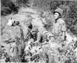 Japanese-American mortar crew of 100th Infantry Battalion, US 442nd Regimental Combat Team firing into suspected German sniper positions, Montenero area, Italy, 7 Aug 1944, photo 1 of 2