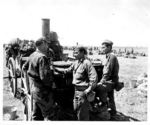 Japanese-American troops of 100th Infantry Battalion, US 442nd Regimental Combat Team inspecting a confiscated German field kitchen, Brescia, Italy, 18 May 1945, photo 1 of 2