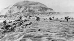 Fifth Division Marines moving inland off the beach, after coming ashore on Iwo Jima, 19 Feb 1945; note Mount Suribachi in background
