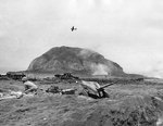 A 37mm gun on Iwo Jima beach with Mount Suribachi in background, 20 Feb 1945; note the TBM Avenger flying overhead