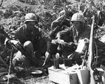 Private First Class H. L. Miles and Corporal C. V. Corley of US Marines rested during a lull in battle, Iwo Jima, Japan, 15 Mar 1945