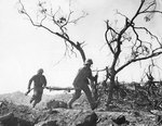 Two US Marines with an empty stretcher ran past a dead Japanese soldier, Iwo Jima, 3 Mar 1945