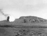 US Fifth Marine Division riflemen waited while a fellow Marine burned out a Japanese-held cave with flame thrower, Iwo Jima, 26 Feb 1945