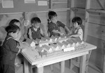 Japanese-American children playing with a scale model of their home at the Tule Lake Relocation Center, Newell, California, United States, 11 Sep 1942