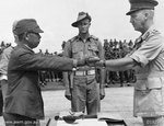 Lieutenant General Hatazo Adachi symbolically surrendered his sword to Australian Major General H. C. H. Robertson at Wom Airstrip, New Guinea, 13 Sep 1945