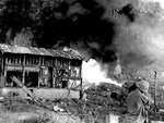 US Marine with flamethrower attacking a Japanese position, northern Saipan, Mariana Islands, 12 Jul 1944; note the scorched building on left
