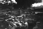 US Marines in a trench at Dutch Harbor, US Territory of Alaska, 3 Jun 1942; note burning fuel tanks in background